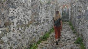 Turista de la mujer que camina en la pared antigua del castillo para tirar una imagen con el mar Mediterráneo tranquilo en fondo metrajes