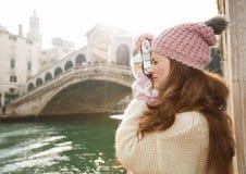 Turista de la mujer que toma las fotos con la cámara retra de la foto en Venecia Foto de archivo libre de regalías