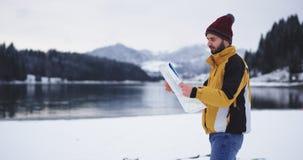 Turista de passeio com um mapa grande e a vista ao redor encontrar seu destino direito, chegou em um lugar bonito com a vídeos de arquivo