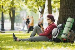 Turista del adolescente de la muchacha con la mochila que mira smartphone en parque de la ciudad Imagen de archivo libre de regalías