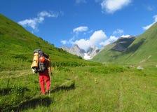 Turista del Backpacker en valle verde de las montañas caucásicas Foto de archivo libre de regalías