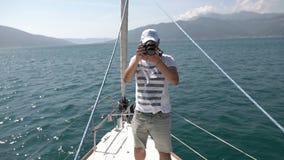 Turista del fotógrafo del viaje del paisaje que toma la foto del barco de navegación almacen de metraje de vídeo