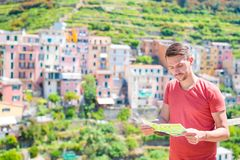 Turista del giovane con il villaggio sbalorditivo del fondo della mappa Turista con la vista scenica di Manarola, Cinque Terre, L fotografie stock libere da diritti
