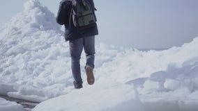 Turista del hombre en el fondo que sube en el top del glaciar Vista que sorprende de un norte o de South Pole nevoso El hielo metrajes