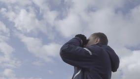 Turista del hombre joven que mira a través de los prismáticos El cielo se nubla el fondo 4k almacen de video