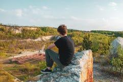 Turista del hombre joven que se sienta en la roca gigante, en el top de la montaña fotografía de archivo
