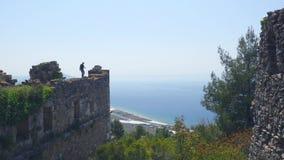 Turista del hombre que camina en la pared antigua del castillo para tirar una imagen con el mar Mediterráneo tranquilo en fondo almacen de video