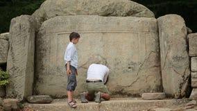 Turista del hombre y del muchacho que explora la estructura antigua Dolmen Teléfono de Selfie almacen de video