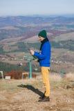Turista del muchacho en montañas con el mapa Imagenes de archivo