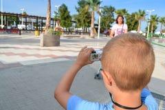 Turista del niño que fotografía un parque con la cámara compacta Imagen de archivo