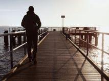 Turista dell'uomo al pilastro di legno del mare Mattina senza vento fredda con luce solare di pendenza Acqua liscia Fotografia Stock Libera da Diritti