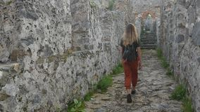 Turista della donna che cammina sulla parete antica del castello per sparare un'immagine con il mar Mediterraneo calmo su fondo stock footage