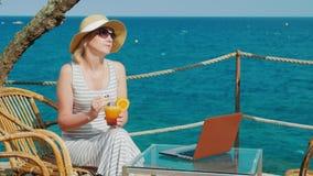 Turista della donna che si rilassa in un caffè con una vista del mare e del cocktail bevente Vicino è un computer portatile sulla archivi video