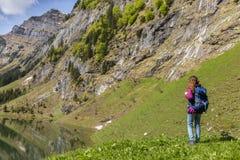 Turista della donna con lo zaino che fa un'escursione sulle alpi Fotografie Stock