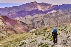 Turista della donna con uno zaino che scala pendio ripido con le belle montagne variopinte dell'Himalaya nei precedenti, Ladakh,  fotografie stock