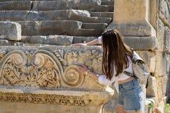 Turista della donna sulle rovine di una città romana antica che esplora e che tocca l'architettura antica in Demre, Turchia immagine stock libera da diritti