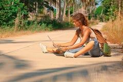 Turista della giovane donna con lo zaino sulla strada Fotografie Stock