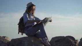 Turista della ragazza che giudica una mappa disponibila e che sogna di nuovi viaggi riposo di seduta della giovane donna sulle ro archivi video