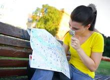 Turista della ragazza con il programma sul banco di sosta Immagini Stock