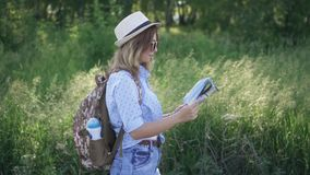 Turista della ragazza con la mappa a disposizione che cammina su un sentiero nel bosco Viaggiatore della giovane donna con uno za video d archivio