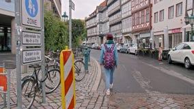 Turista della ragazza con uno zaino che cammina giù la via Va a partire dalla macchina fotografica Via con le casette lento video d archivio