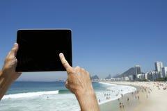 Turista di viaggio che per mezzo della compressa a Rio de Janeiro Brazil Beach Immagini Stock