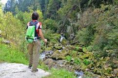 Turista do caminhante do homem na roupa brilhante com um suporte da vara na montanha, olhando a cachoeira e as montanhas de pedra foto de stock royalty free