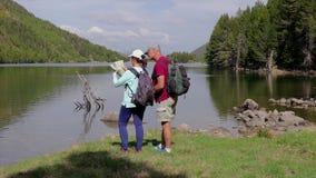 Turista dos que mira un mapa al lado del lago almacen de video
