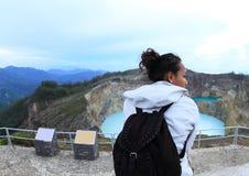 Turista em Kelimutu que olha a torneira e a lata originais dos lagos imagem de stock