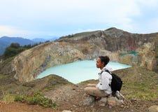 Turista em Kelimutu que olha a torneira e a lata originais dos lagos fotografia de stock