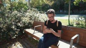 Turista em um banco com um smartphone video estoque