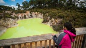 Turista en la piscina de la cueva del ` s del diablo en Rotorua fotografía de archivo libre de regalías