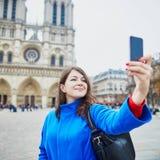 Turista en París, haciendo el selfie divertido cerca de la catedral de Notre-Dame Foto de archivo libre de regalías