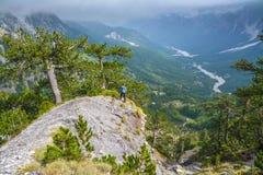 Turista en un acantilado sobre el valle de la montaña imágenes de archivo libres de regalías