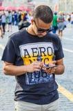 Turista en una camiseta AERO- NYC 1987 con un smartphone en sus manos que camina en cuadrado rojo Imagen de archivo libre de regalías