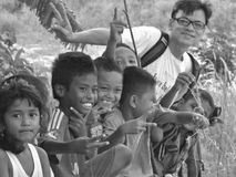Turista entre niños del pueblo Fotos de archivo