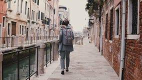 Turista europeo elegante joven feliz de la mujer con la cámara que disfruta de caminar a lo largo de la calle vieja famosa del ca almacen de video