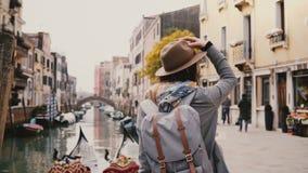 Turista europeo elegante joven feliz de la mujer en sombrero que disfruta de la mirada alrededor de hacer una pausa los canales f metrajes