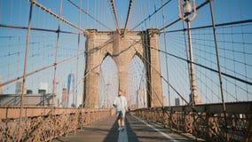 Turista europeo masculino positivo que camina hacia cámara, sonriendo y mirando alrededor a lo largo del puente de Brooklyn, Nuev almacen de metraje de vídeo