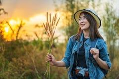 Turista fêmea com trouxa e câmera no campo com por do sol fotografia de stock
