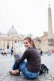Turista fêmea consideravelmente novo que estuda um mapa Fotografia de Stock Royalty Free