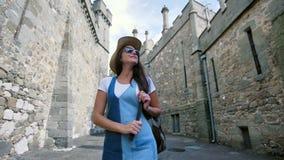 Turista fêmea de sorriso feliz do mochileiro nos óculos de sol e no chapéu que aprecia a arquitetura antiga video estoque