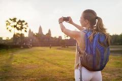 Turista fêmea novo que toma a imagem de Angkor Wat em Camboja Fotografia de Stock Royalty Free