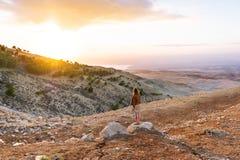 Turista fêmea que olha uma paisagem de nivelamento bonita no deserto de Jordânia foto de stock