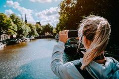 Turista fêmea que toma a foto do canal em Amsterdão no telefone celular Luz solar morna da tarde do ouro Curso em Europa imagens de stock