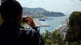 Turista fêmea que toma a foto do lugar, de iate e do navio sightseeing agradáveis no porto filme