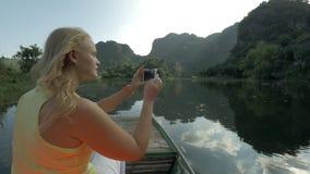 Turista fêmea tomando fotos com pilha durante o barco em Trang, Vietname filme