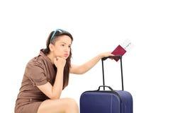 Turista fêmea triste que guarda um passaporte e uma espera Fotos de Stock Royalty Free