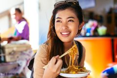 Turista f?mea novo que come o macarronete do tailand?s da almofada na loja fotografia de stock royalty free