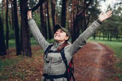 Turista felice della donna che cammina nella foresta di primavera e che solleva sentiresi libero di armi Concetto di turismo e di immagine stock